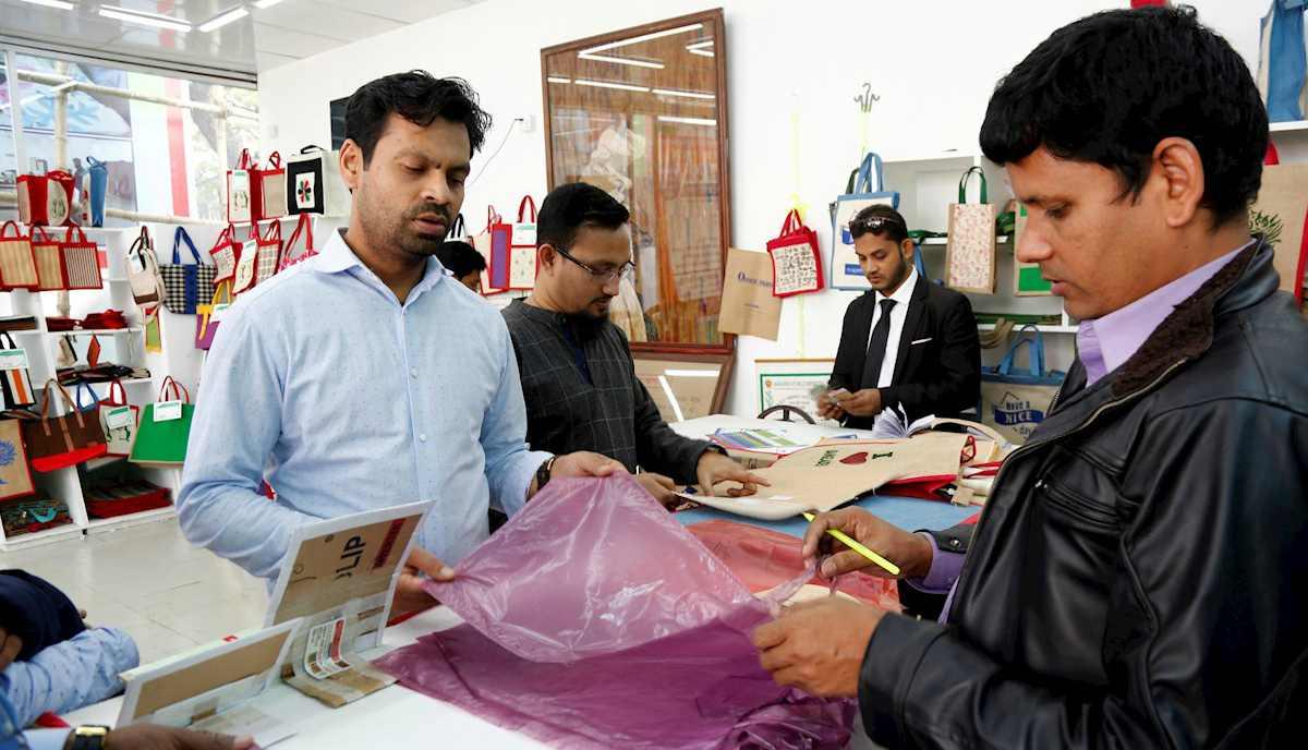 Personas miran las bolsas de yute cuando visitan el puesto de Bangladesh Jute Mills Corporation (BJMC) en Dacca. Bangladesh, uno de los países más contaminados del mundo, está tratando de dejar de depender de los plásticos de un solo uso con una bolsa de embalaje biodegradable hecha de celulosa de yute. (Foto: EFE / EPA / ALAMINA MONIRUL)